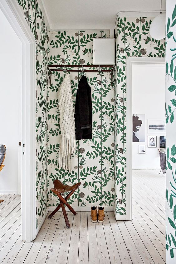 a Nordic entryway with a botanical print wallpaper statement wall that spruces up the space
