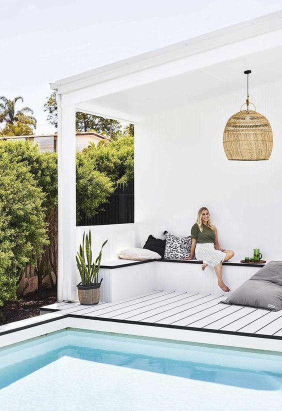a contemporary tropical pool cabana in white, with black surfaces, a wicker lamp and potted plants
