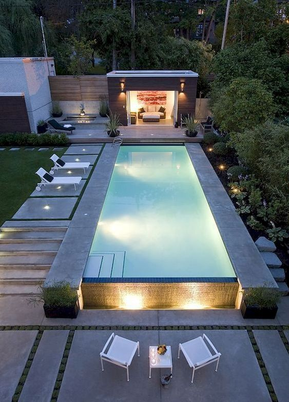 a minimalist pool deck with loungers and some chairs with a table plus lights all over