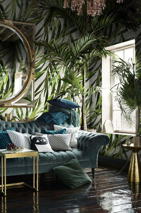 a gorgeous living room with botanical print wallpaper, muted color furniture and glam gold touches