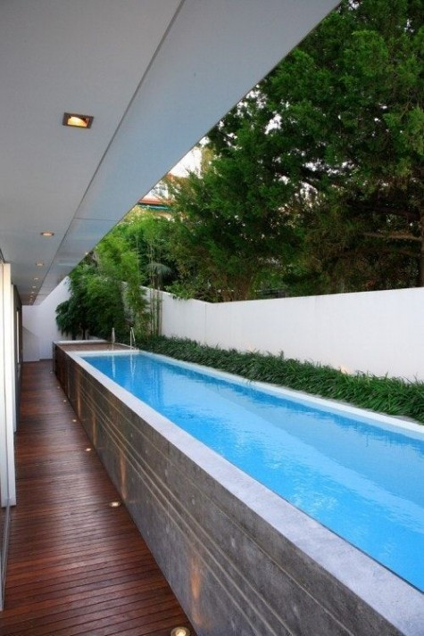 a long narrow pool raised up the deck for comfortable using and grass to line it up and add a fresh feel