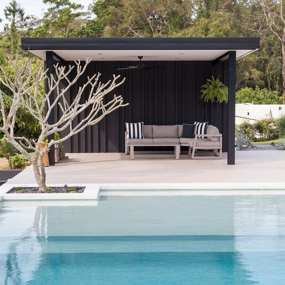 a minimalist black pool cabana with striped pillows on a single upholstered sofa for those who dont' like anything excessive