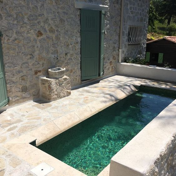 a small and rustic backyard done with stone and a narrow and long pool that will refresh you