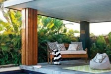 07 a wooden bench with pillows and a bean bag chair for a contemporary chic and stylish pool deck