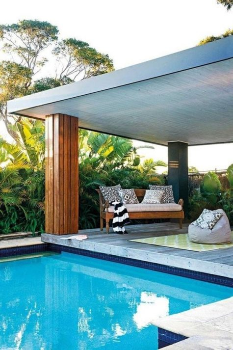 a wooden bench with pillows and a bean bag chair for a contemporary chic and stylish pool deck