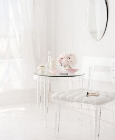 a clear acrylic chair and a matching table for an ethereal vanity space