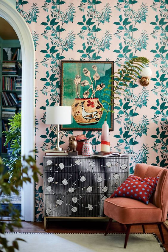 a colorful mid-century modern space with pink botanical wallpaper and a striped botanical sideboard