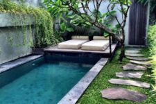 08 a long pool clad with stone tiles with a small wodoen deck over it, some greenery and a couple of loungers