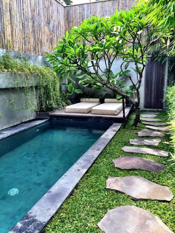 a long pool clad with stone tiles with a small wodoen deck over it, some greenery and a couple of loungers