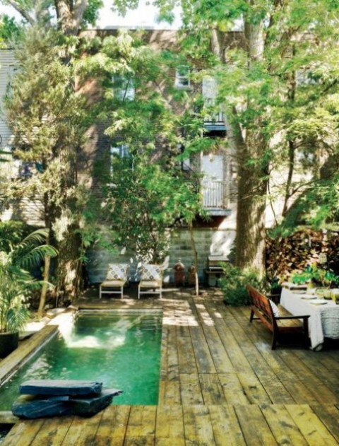 a tropical inspired deck clad with reclaimed wood, loungers and comfy stained furniture plus a long yet narrow pool done with green tiles