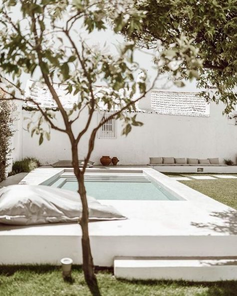 lots of pillows instead of furniture, vases and lanterns for a stylish minimalist pool deck