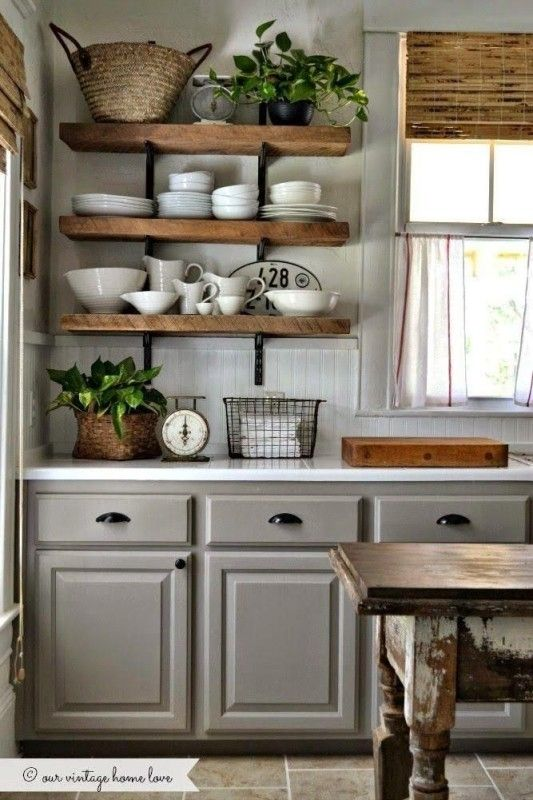traditional grey cabinets with rough wood shelving that makes the space less formal and cozier