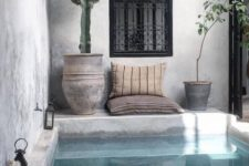 09 a boho chic backyard done in concrete and plaster, with a plunge pool, pillows, potted cacti and lanterns