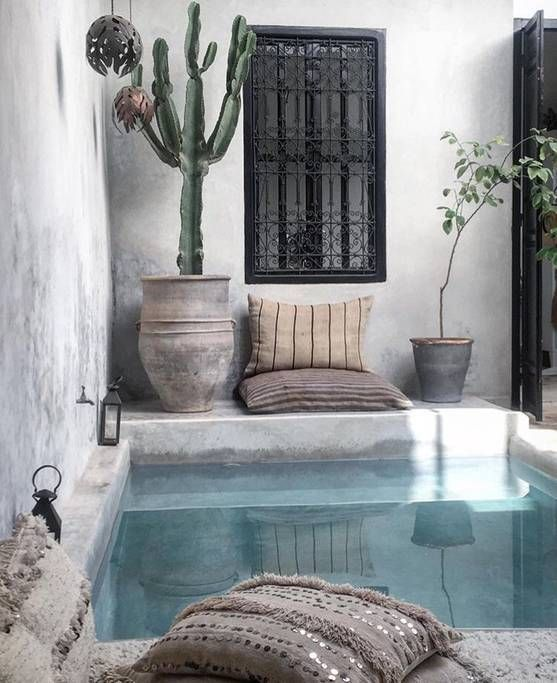 a boho chic backyard done in concrete and plaster, with a plunge pool, pillows, potted cacti and lanterns