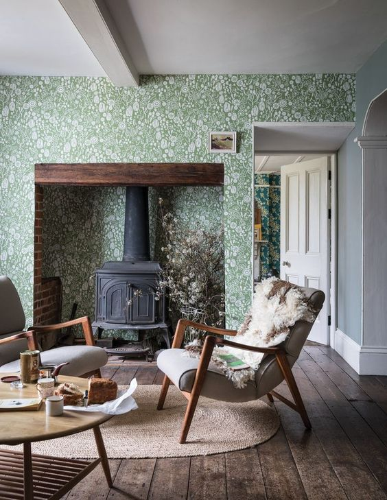 a cozy living room with green and white botanical wallpaper, a vintage hearth and grey chairs