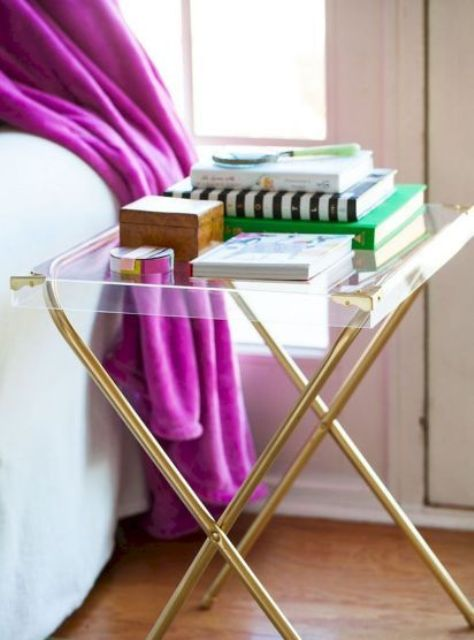 a glam nightstand or side table of brass legs and an acrylic tabletop is a super modern idea