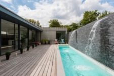 09 a long wooden deck and a long and narrow pool with two waterfalls look like an ultimate relaxation oasis