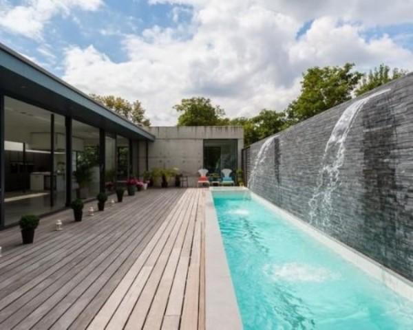 a long wooden deck and a long and narrow pool with two waterfalls look like an ultimate relaxation oasis
