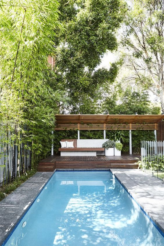 a modern farmhouse cabana with potted plants, a stained wooden bench and a large deck by the pool