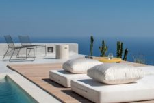 09 mattresses with pillows and some chairs with a coffee table are a cool setup for a minimalist pool deck