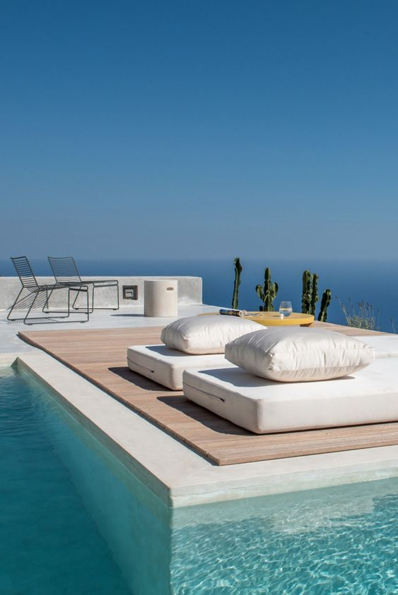 mattresses with pillows and some chairs with a coffee table are a cool setup for a minimalist pool deck