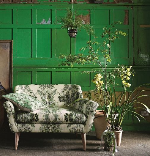 a botanical love seat on wooden legs in front of an emerald wall is a gorgeous idea