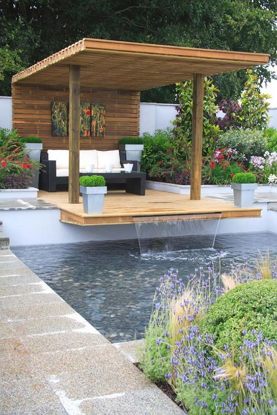 a pool cabana paired with a deck over the pool features a waterfall, potted plants and blooms, dark wicker furniture