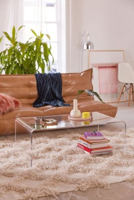 a simple curved acrylic coffee table looks ethereal and makes all the items look floating