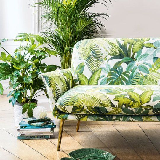 a chic botanical love seat on gilded legs and greenery in pots for creating a natural feel