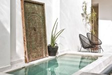 11 a fantastic Moroccan inspired backyard with a small white pool, a vintage wooden door, wicker and rattan furniture