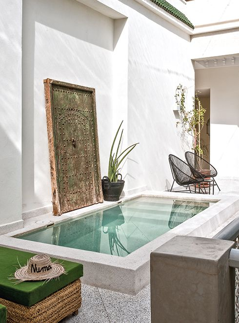 a fantastic Moroccan inspired backyard with a small white pool, a vintage wooden door, wicker and rattan furniture