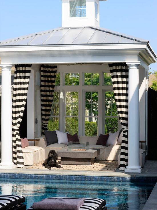 a small and comfy pool cabana with upholstered furniture, a concrete coffee table with a fireplace, printed curtains and a mirror wall