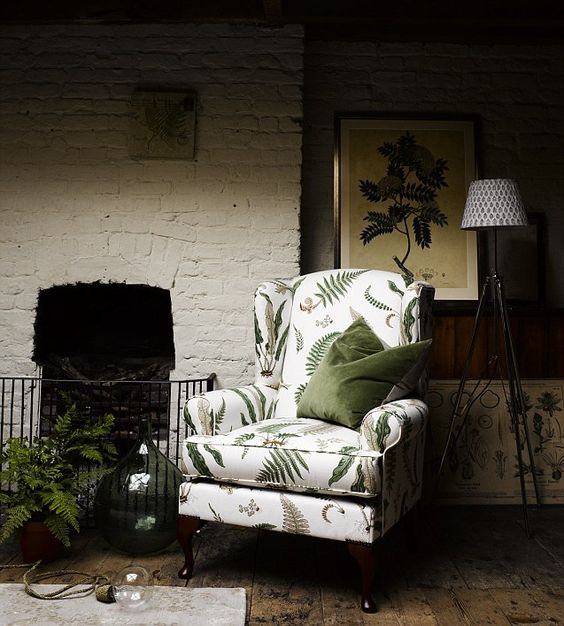 a moody living room with a vintage whiet chair with a tropical leaf print that looks old-fahsioned yet modern