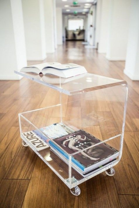 an acrylic coffee table on casters with magazine storage and sheer wheels is a very functional option