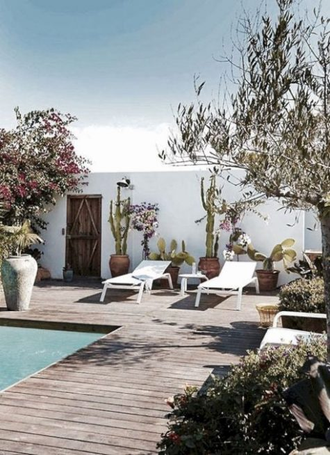 white loungers and a side table, potted plants and blooms for a simple boho and desert-inspired pool deck