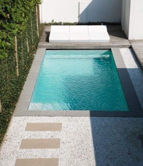 a gorgeous minimalist space with a wooden deck, tiled pathways and a small pool clad with grey tiles around