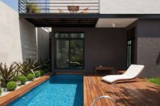 13 a modern stained deck with a long and narrow pool clad with mosaic tiles, planted greenery for a fresh touch