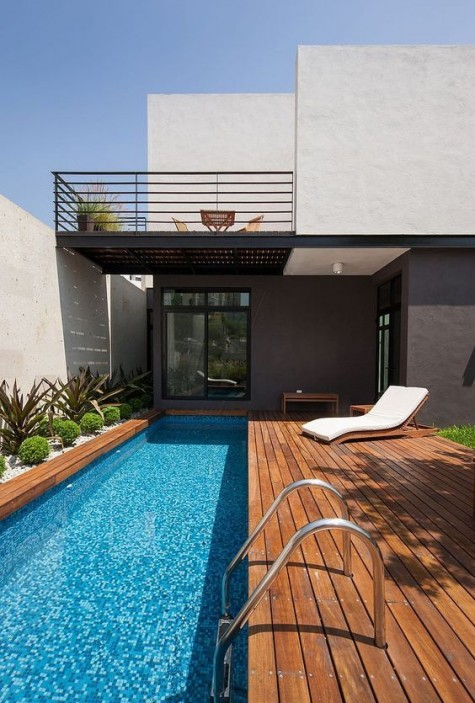 a modern stained deck with a long and narrow pool clad with mosaic tiles, planted greenery for a fresh touch