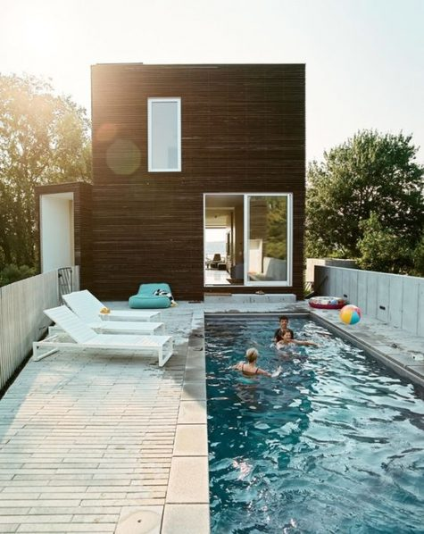 white loungers and a turquoise bean bag chair for a long and narrow pool deck