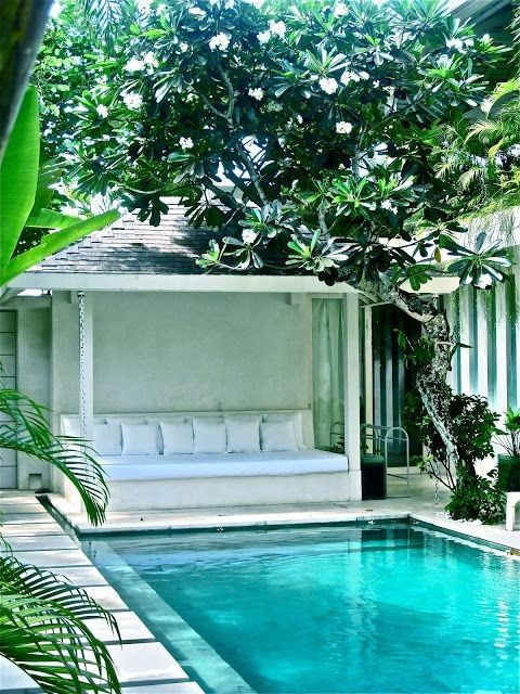 a small pool cabana with a single built-in bench and white pillows is all you need for maximal comfort