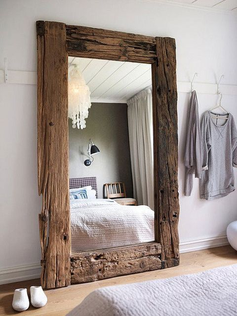 an oversized mirror with rough wooden frames is a great piece for a rustic and boho space