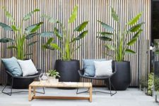 14 wicker chairs, a wooden coffee table and some potted plants for a cozy contemporary pool deck space