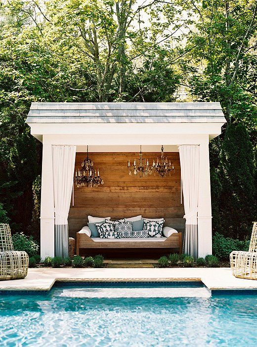 a small rustic pool cabana with a single wooden bench with pillows, elegant crystal chandeliers, plants around and curtains