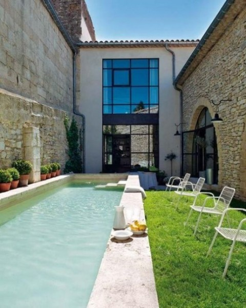 a welcoming backyard with chairs and a long and narrow pool clad with stone, green grass for a fresh touch