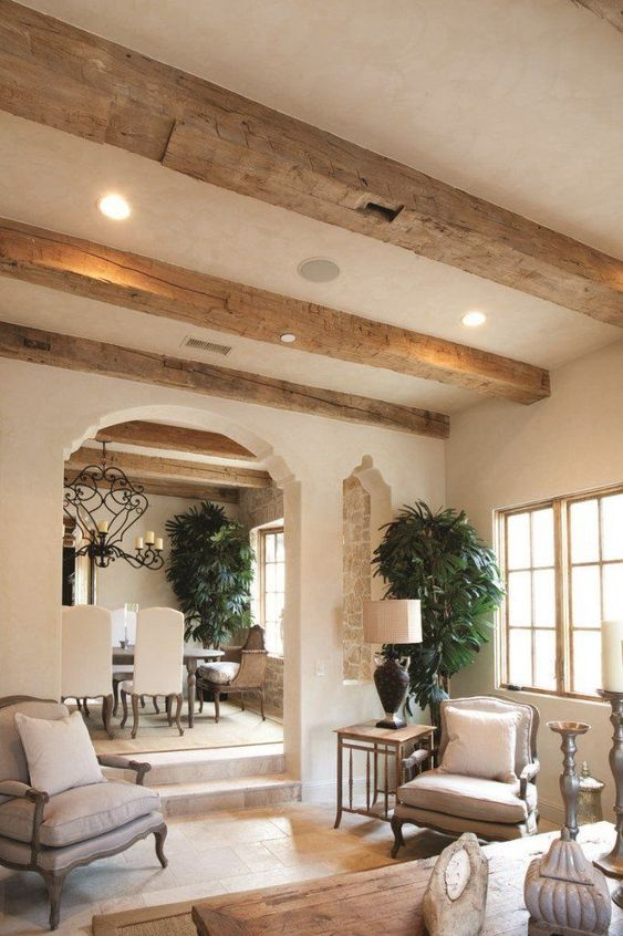 rough wooden beams on the ceiling highlight the cozy vintage-inspired style of the room