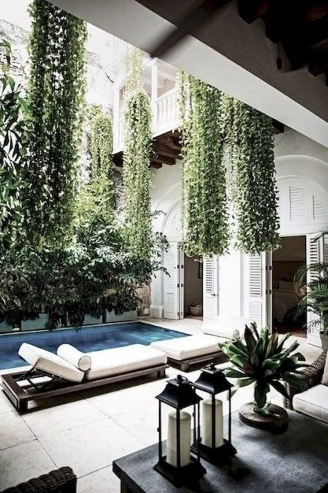 a comfortable lounger, hanging greenery, candle lanterns and potted plants create a somewhat tropical feel