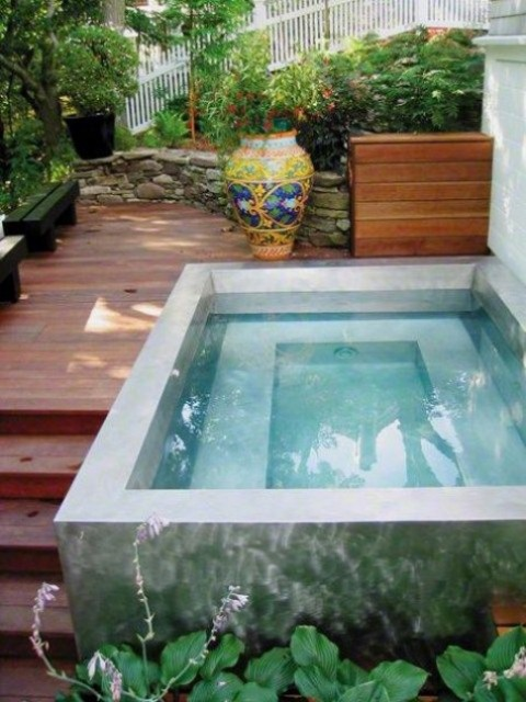 a small and comfy wooden deck plus benches and a neutral stone swimming pool with inner lights to enjoy plunging at night, too