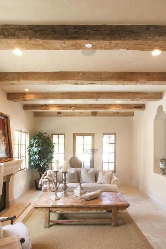 rough wooden beams with lights and a wooden table for creating a Provence-inspired space with a cozy rustic feel