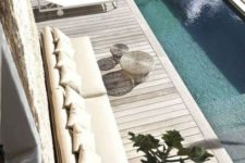 17 a contemporary pool deck with a long sofa, some coffee tables, loungers and chairs plus a coffee table