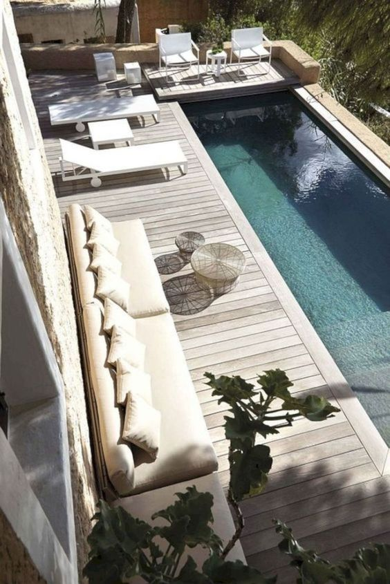 a contemporary pool deck with a long sofa, some coffee tables, loungers and chairs plus a coffee table